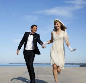 Newlyweds running on a beach