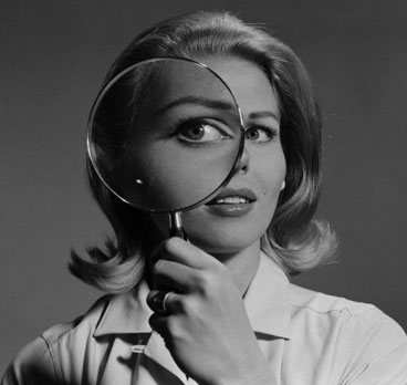 Blond woman magnifying glass held up to and enlarging one eye