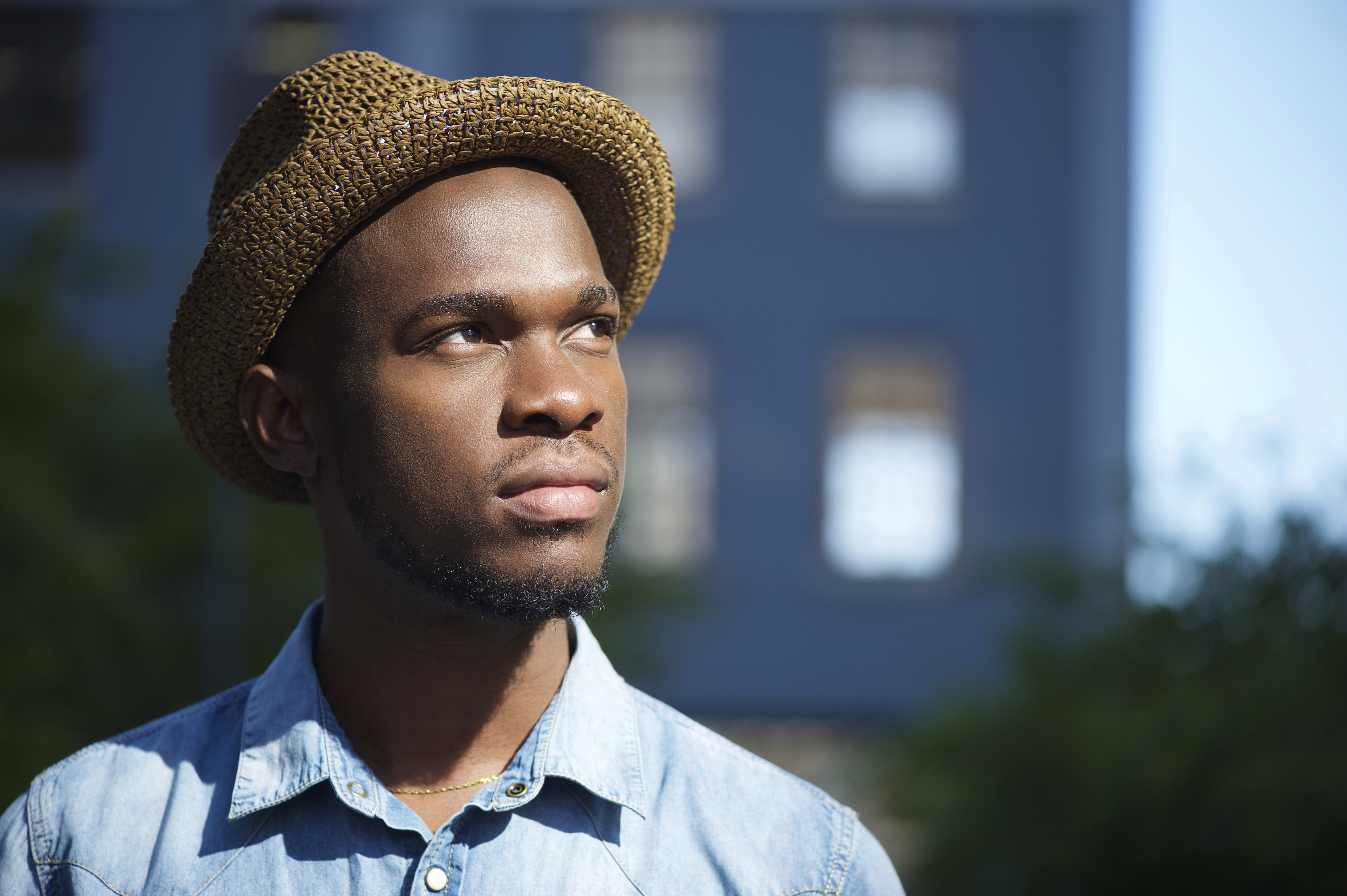 Close up of a young man wearing a hat, building in background.