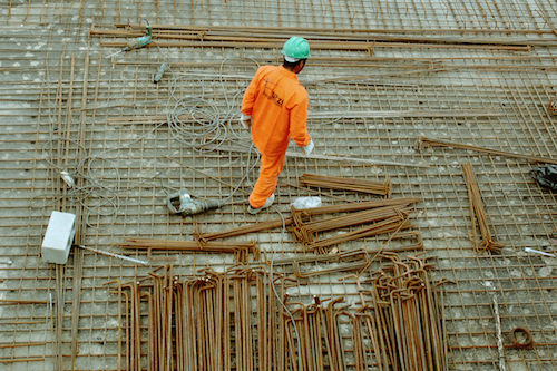 A construction worker in a green helmet and orange jumpsuit works on the worksite.