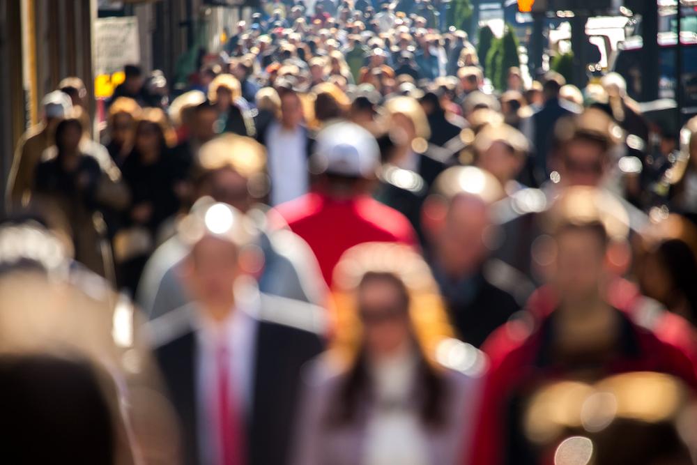 Anonymous crowd of people walking on New York City street sidewalk