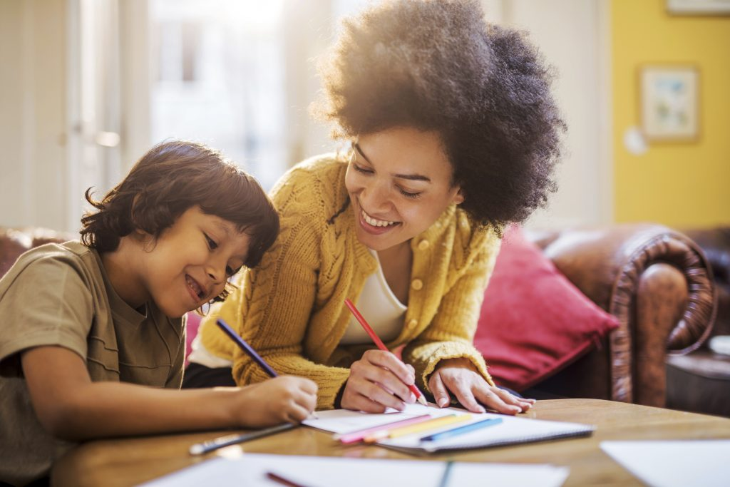 Young happy African American mother having fun with his son at home while coloring together.
