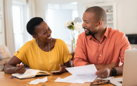 Cheerful mature couple sitting and managing expenses at home. Happy african man and woman paying bills together and managing budget. Black smiling couple checking accountancy and bills while looking at each other. (Cheerful mature couple sitting and m