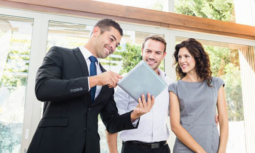 A real estate agent shows two clients listing information on a tablet