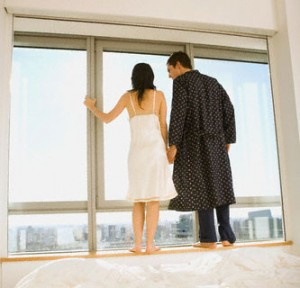Hispanic couple looking out window