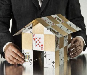 Businessman holding door open to gold house of cards